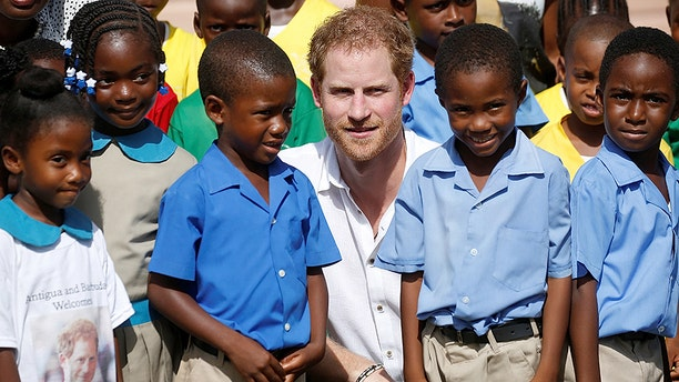 Prince Harry poses for a photo with school children as he tours Holy Trinity Primary school during his official visit to Codrington, Barbuda November 22, 2016. REUTERS/Carlo Allegri - RC13F9E8B580