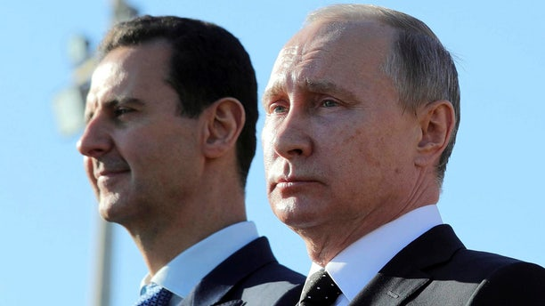 Russian President Vladimir Putin alongside Syrian President Bashar al-Assad during a visit the Hmeymim air base in Latakia Province, Syria on Dec. 11, 2017.