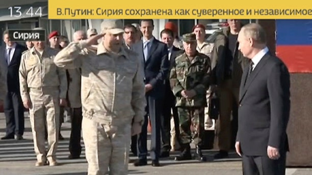 Sergei Surovikin, Russian Commander in Syria, 3rd left, reports to President Vladimir Putin, right, as Syrian President Bashar Assad, 4th left, listens, at the Hemeimeem air base in Syria.