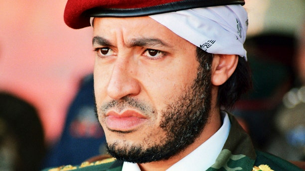 FILE - In this undated photo made available Sunday, Sept. 25, 2011, al-Saadi Gadhafi, son of Libyan leader Muammar Qaddafi, watches a military exercise by the elite military unit commanded by his brother, Khamis, in Zlitan - 90 miles southeast of Tripoli, Libya. Muammar Qaddafi's son, al-Saadi, has denied allegations of corruption and intimidation and says an Interpol decision to put him on the equivalent of its most-wanted list is political.