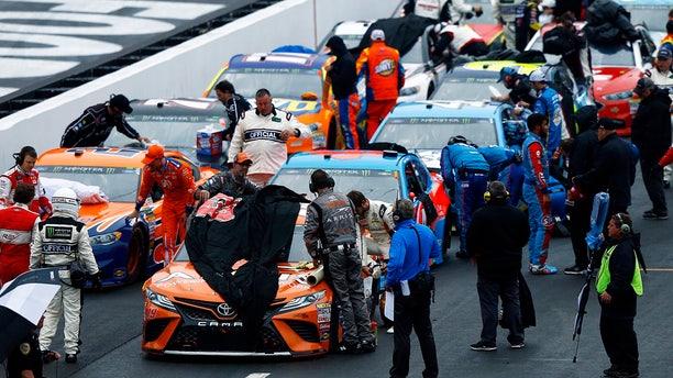 Crews cover the cars as rain falls during a NASCAR Cup Series auto race, Sunday, April 15, 2018, in Bristol, Tenn. (AP Photo/Wade Payne)
