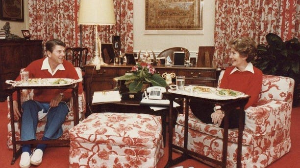 President Ronald Reagan and First Lady Nancy Reagan eat on TV trays in the White House, in 1981.
