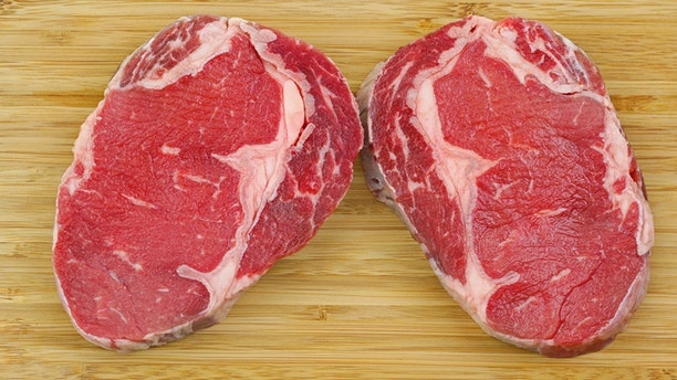 A cut of outer side of the rib : prime Rib Eye steak on a wooden cutting board isolated on a white background