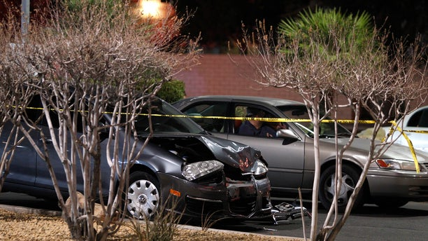 FILE - In this Jan. 21, 2014 file photo, a damaged car is seen at the scene of a fatal road rage incident near the corner of Tropicana Avenue and Rainbow Boulevard in Las Vegas. Authorities say a man shot a motorist to death in a vehicle with two children in the backseat in an apparent road-rage confrontation during rush-hour several miles west of the Las Vegas Strip. Nearly eight of every 10 U.S. drivers admit expressing anger, aggression or road rage at least once in the previous year, according to a new survey released Thursday, July 13, 2016, by the AAA Foundation for Traffic Safety. It could be following too closely, yelling at another driver, cutting them off or making angry gestures. (John Locher/Las Vegas Review-Journal via AP, File)