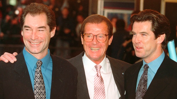 """In this Sunday, Nov. 17, 1996 file photo, three of the actors who played James Bond, Timothy Dalton left, Roger Moore, center, and Pierce Brosnan, at a London cinema to celebrate the life of Albert R. """"Cubby"""" Broccoli, the American film producer behind seventeen Bond movies."""