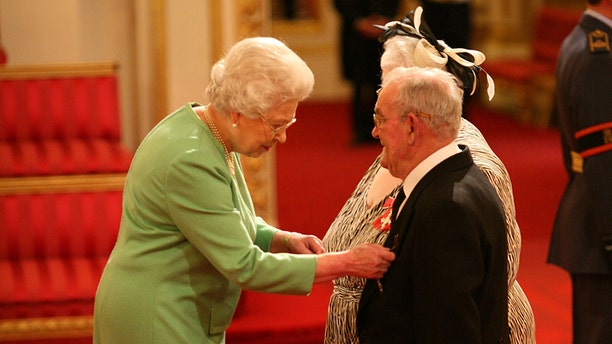 Penelope Jones and Ronald Jones as they receive their MBEs from Queen Elizabeth II at Buckingham Palace.