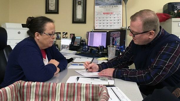 David Ermold, right, files to run for Rowan County Clerk in Kentucky as Clerk Kim Davis looks on Wednesday.