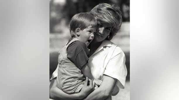 Young Prince Harry, 3, yawns as his mother Princess Diana holds him during a morning picture session at Marivent Palace.