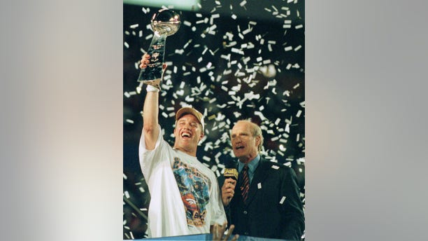 John Elway holds up the Vince Lombardi Trophy as he is interviewed by former Steelers quarterback and broadcaster Terry Bradshaw after leading his Denver Broncos team to a second consecutive Super Bowl victory, January 31