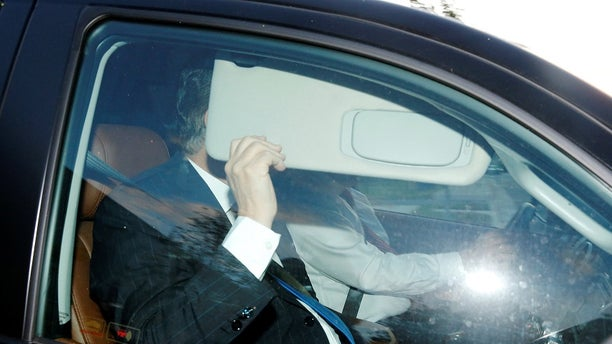 Former Trump campaign chairman Paul Manafort, one focus of Special Counsel Robert Mueller's investigation into alleged Russian meddling in the 2016 presidential election, hides behind a car visor as he leaves his home in Alexandria, Va., after being asked to surrender to federal authorities.