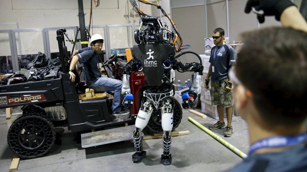 """File photo: The Team IHMC Robotics Atlas """"Running Man"""" robot built by Boston Dynamics is readied in the team garage during the finals of the Defense Advanced Research Projects Agency (DARPA) Robotic Challenge in Pomona, California June 6, 2015. (REUTERS/Patrick T. Fallon)"""