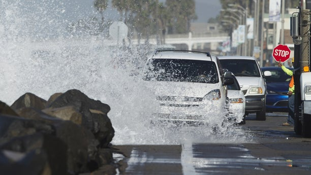 Drivers make their way along a beach road as a wave crashes onto the street due to a combination of high tides and high surf in Oceanside, California October 27, 2015.