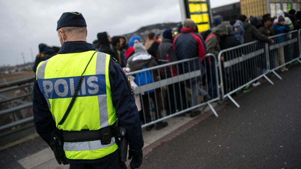A police officer keeps guard as migrants arrive at Hyllie station outside Malmo, Sweden. Picture taken November 19, 2015. REUTERS/Johan Nilsson/TT NEWS AGENCY    ATTENTION EDITORS - THIS IMAGE WAS PROVIDED BY A THIRD PARTY. FOR EDITORIAL USE ONLY. NOT FOR SALE FOR MARKETING OR ADVERTISING CAMPAIGNS. THIS PICTURE IS DISTRIBUTED EXACTLY AS RECEIVED BY REUTERS, AS A SERVICE TO CLIENTS. SWEDEN OUT. NO COMMERCIAL OR EDITORIAL SALES IN SWEDEN. NO COMMERCIAL SALES. - RTX24DEM