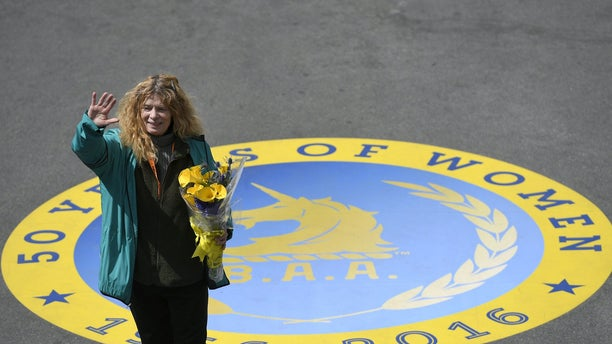 """Roberta """"Bobbi"""" Gibb , the first woman to finish the Boston Marathon 50 years ago in 1966, waves to the crowd after ceremonially breaking a finish-line tape during the 120th running of the Boston Marathon in 2016."""