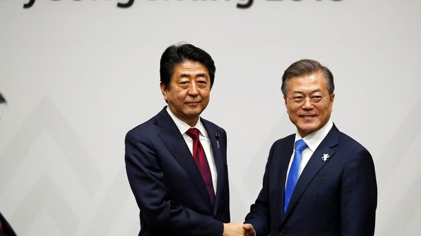 Japanese Prime Minister Shinzo Abe, left, greeted by South Korean President Moon Jae-in at the Winter Olympics.