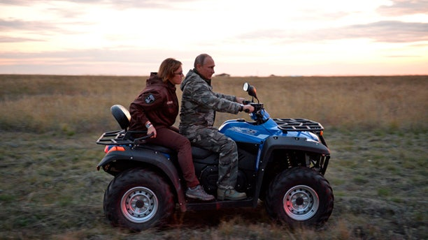 Russian President Vladimir Putin rides a quad bike as he visits a reserve for wild horses near the Urals city of Orenburg, about 800 miles southeast of Moscow, Russia, Monday, Oct. 3, 2016.