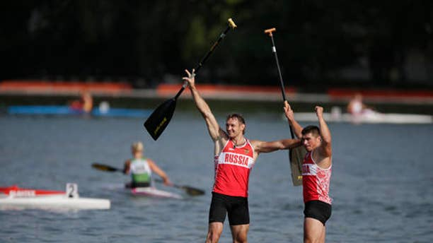 Nikolay Lipkin, left, and Andrey Kraitor of Russia celebrate after they won the C1 relay men 200m final of the ICF Canoe Sprint World Championships 2014 in Moscow, Russia, on Aug. 10, 2014. The International Canoe Federation says it has barred five Russian competitors from the Rio Olympics.