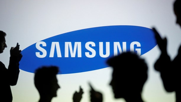 People are silhouetted as they pose with mobile devices in front of a screen projected with a Samsung logo, in this picture illustration taken in Zenica October 29, 2014. (REUTERS/Dado Ruvic/Illustration/File Photo)