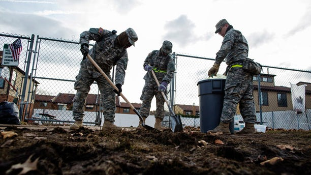 Nov. 15, 2012: National Guard troops work to clean sidewalks of storm debris from Hurricane Sandy in the Staten Island borough neighborhood of New Dorp Beach in New York.