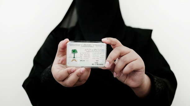 In this June 23, 2018 photo, 27-year old Mabkhoutah al-Mari poses for a photograph holding her new car license at the Saudi Driving School inside Princess Nora University in Saudi Arabia.