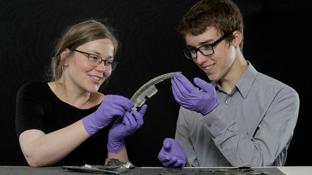David Hall and Alice Blackwell, Glenmorangie Research Fellow at National Museums Scotland, examine a silver fragment.