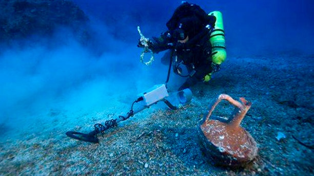 In this undated photo provided by Argo via the Greek Culture Ministry, a diver with a metal detector holds a copper ship's fitting next to a vase at the site of the Antikythera wreck off the island of Antikythera in southern Greece.