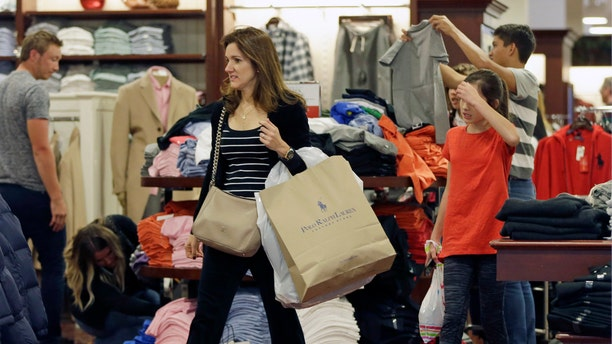 A shopper carries a bag with merchandise at a Polo Ralph Lauren store on Black Friday.