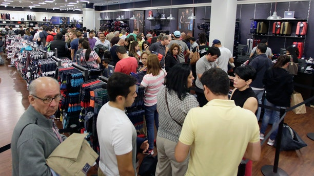Shoppers stand in line to pay for their purchased merchandise at a Tommy Hilfiger store on Black Friday, Nov. 25, 2016, in Miami. Stores opened their doors Friday for what is still one of the busiest days of the year, even as the start of the holiday season edges ever earlier. (AP Photo/Alan Diaz)