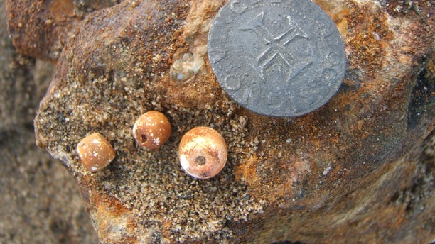A coin and rosary beads discovered in the Namibian shipwreck (Dieter Noli).
