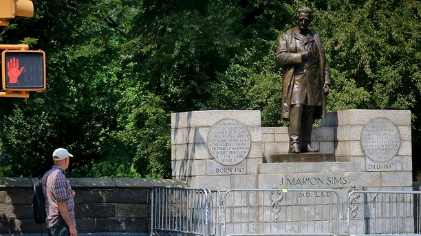 A man looks at the statue of Dr. J. Marion Sims in New York's Central Park.