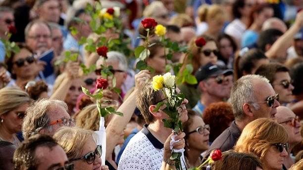 People in Barcelona held flowers during a demonstration condemning last week's terror attacks that killed at least 15 people.