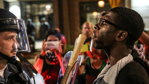 A protester confronts a police officer in St. Louis, Missouri during a night of demonstrations following a cop's acquittal in the shooting death of a black man.