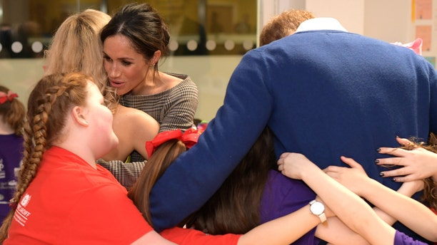 Prince Harry and Markle receive hugs from Star Hub children.