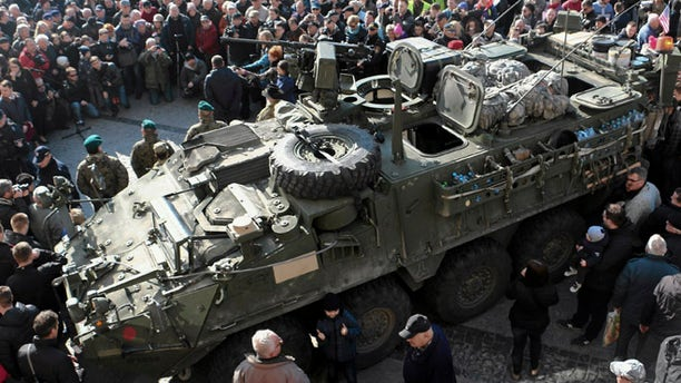 "March 24, 2015: People gather around an U.S. Army 2nd Cavalry Regiment ""Stryker"" armored fighting vehicle in Bialystok, Poland, which is a part of the U.S. military ""Dragoon Ride"" operation. Dragoon Ride is aimed at demonstrating commitment to NATO allies in light of Russia's aggression in Ukraine, according to the U.S. Army."