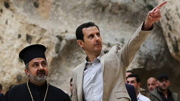 April 20, 2014: In this file photo, released by the Syrian official news agency SANA, Syrian President Bashar Assad, right, visits the Christian village of Maaloula, near Damascus, Syria.