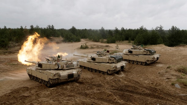 """U.S. M1 Abrams tanks fire during the """"Saber Strike"""" NATO military exercise in Adazi, Latvia, June 11, 2016."""