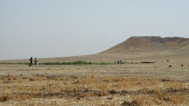 Archaeologists inspect the mound at Tell Brak, in northeastern Syria. The 283 million cubic foot (8 million cubic meter) mound is entirely artificial, accumulating over 6,000 years, as residents built on top of old mud brick buildings.