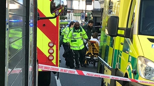 Emergency services help a person after a fire at Parsons Green underground station in London, Britain.
