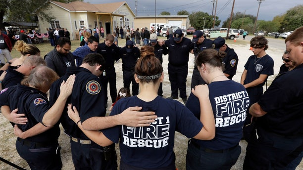 First responders join in prayer following a Veterans Day event, Saturday, Nov. 11, 2017, near the Sutherland Springs First Baptist Church, in Sutherland Springs, Texas.