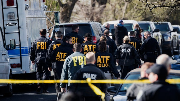 ATF agents descend on the site of one of the Austin package explosions on Monday.