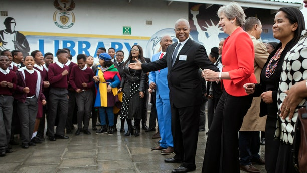 British Prime Minister Theresa May, second from right, dances with pupils during a visit at the the ID Mkhize High School in Gugulethu, Cape Town, South Africa, Tuesday, Aug. 28, 2018.