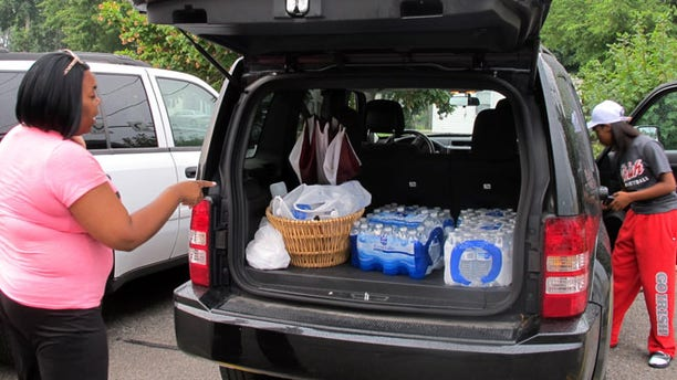 Aug 2, 2014: Aundrea Simmons stands next to her minivan with cases of bottled water she bought after Toledo warned residents not to use its water in Toledo, Ohio.