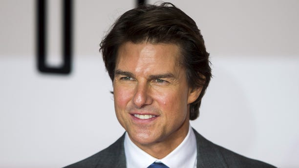 """July 25, 2015. U.S. actor Tom Cruise poses for photographers at a British screening of the film """"Mission Impossible: Rogue Nation"""" in London."""