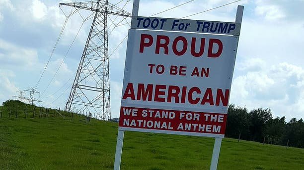 "Simmons' most recent sign, which gained attention, said: ""We stand for the national anthem."""