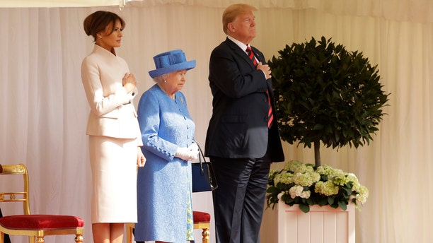 First Lady Melania Trump, left, Queen Elizabeth II, center, and President Trump, right, stand for the National Anthem at Windsor Castle.