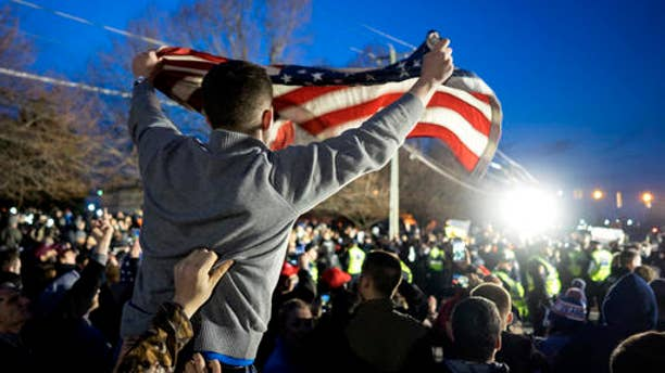 A Donald Trump supporter waves an American flag at a Trump campaign rally in Bethpage, N.Y., April 6, 2016.