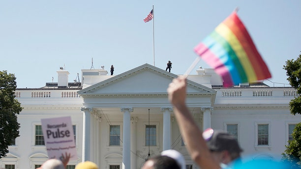 In this Sunday, June 11, 2017 file photo, Equality March for Unity and Pride participants march past the White House in Washington.