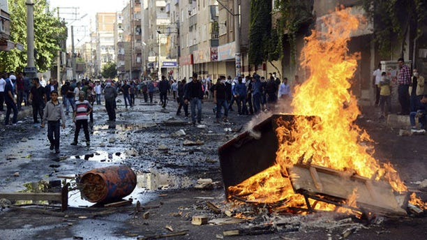Kurdish protesters set fire to a barricade set up to block the street as they clash with riot police in Diyarbakir, Turkey. (Reuters)