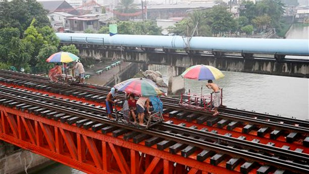 "Oct. 17, 2015: Commuters ride on a locally-built cart known as ""trolley"" which makes use of a railroad track on a typhoon-induced rain in Manila, Philippines."