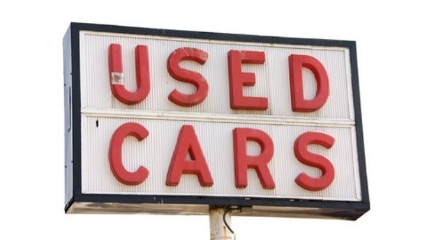 This is a picture of an old used cars sign with red letters, isolated on a white background.